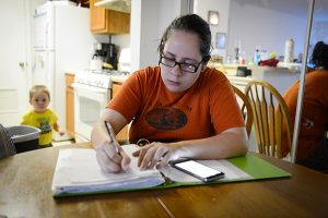 Photo: Rachel S. O'Hara/Sarasota Herald-TribuneJennifer tries to pay bills and go through some paperwork while her son, David, 2, competes for her attention.