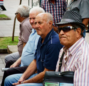 Row of older men sitting on a bench